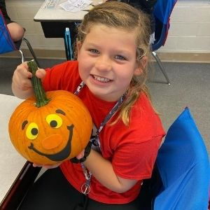 Student posing with pumpkin